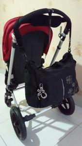 Tas digantung dengan cara disampirkan di stroller dengan handle bar (pegangan) menyatu